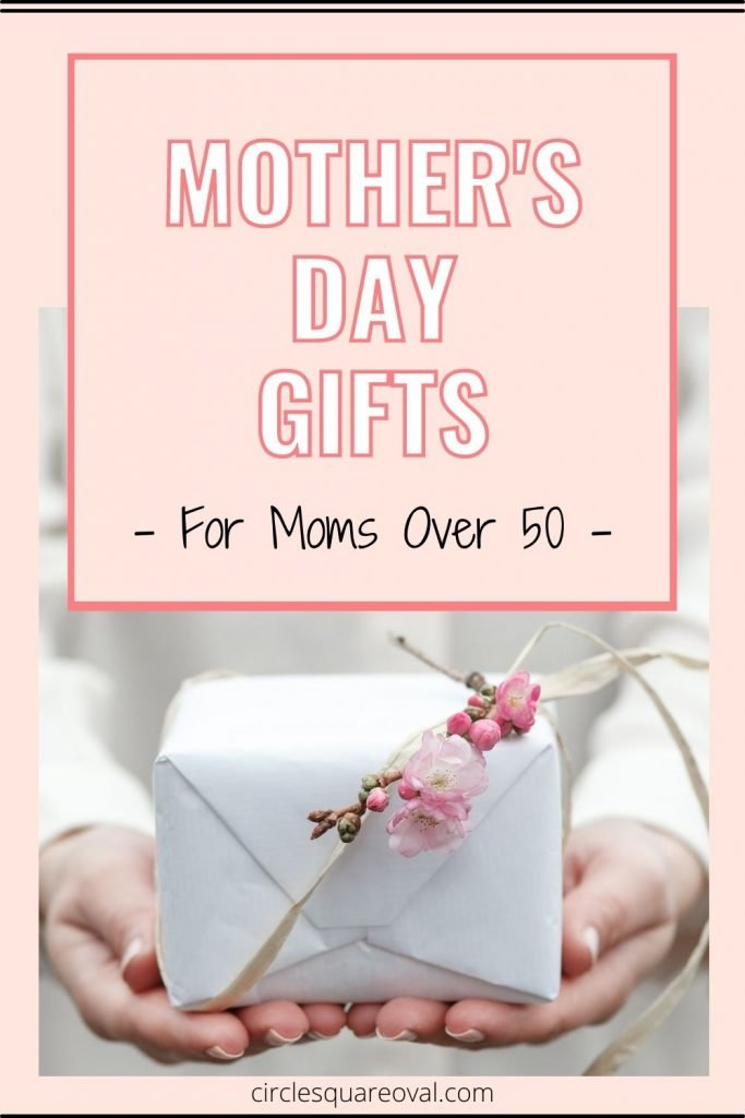 woman holding wrapped box with floral sprig as a mother's day gift for mom over fifty