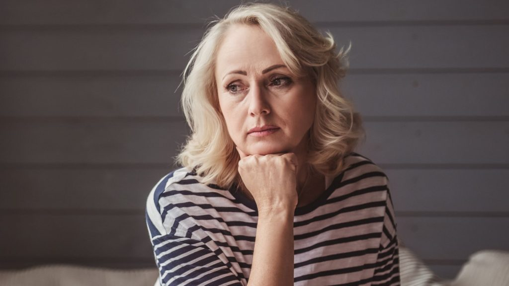 blonde woman with chin on fist, thinking about a difficult conversation with her partner