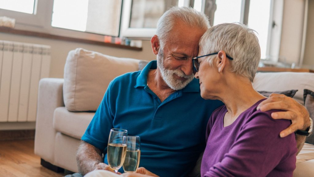 older couple hugging and drinking champagne after resolving a difficult conversation