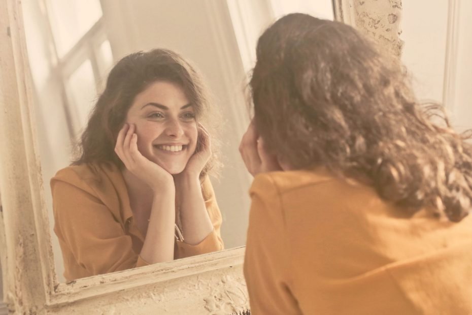 woman smiling at image in mirror