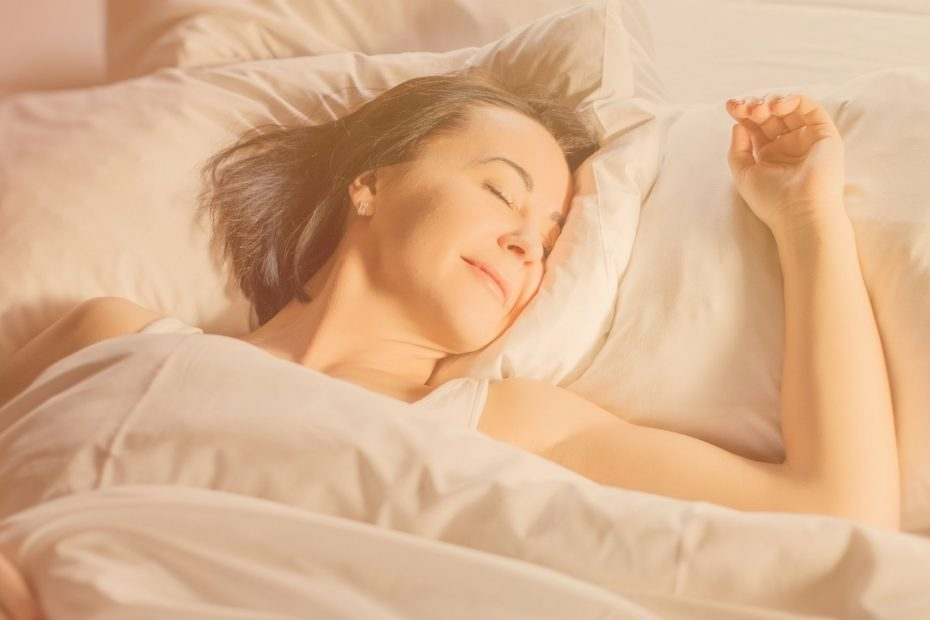 woman smiling as she sleeps soundly