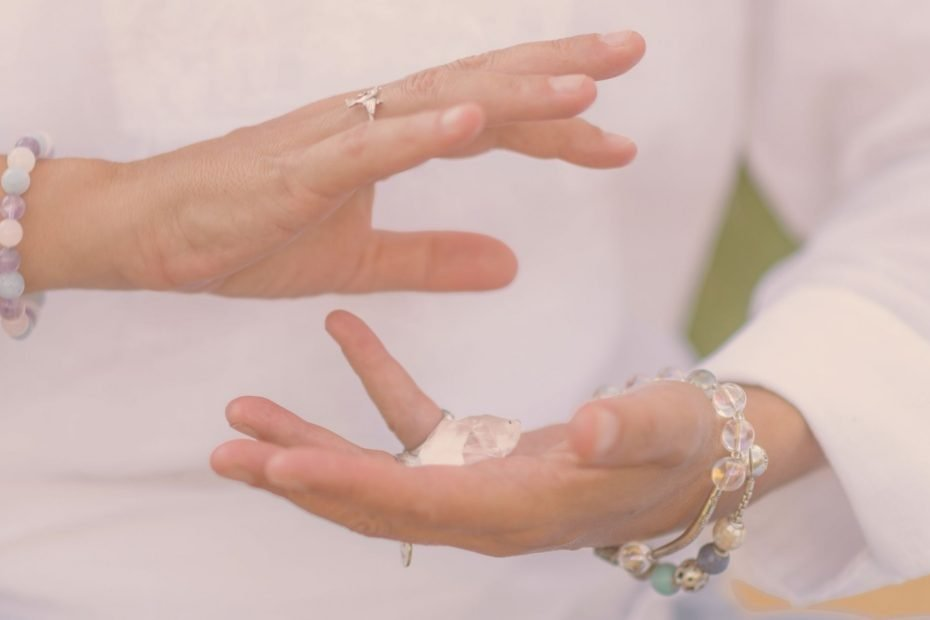 hands meditating with crystal