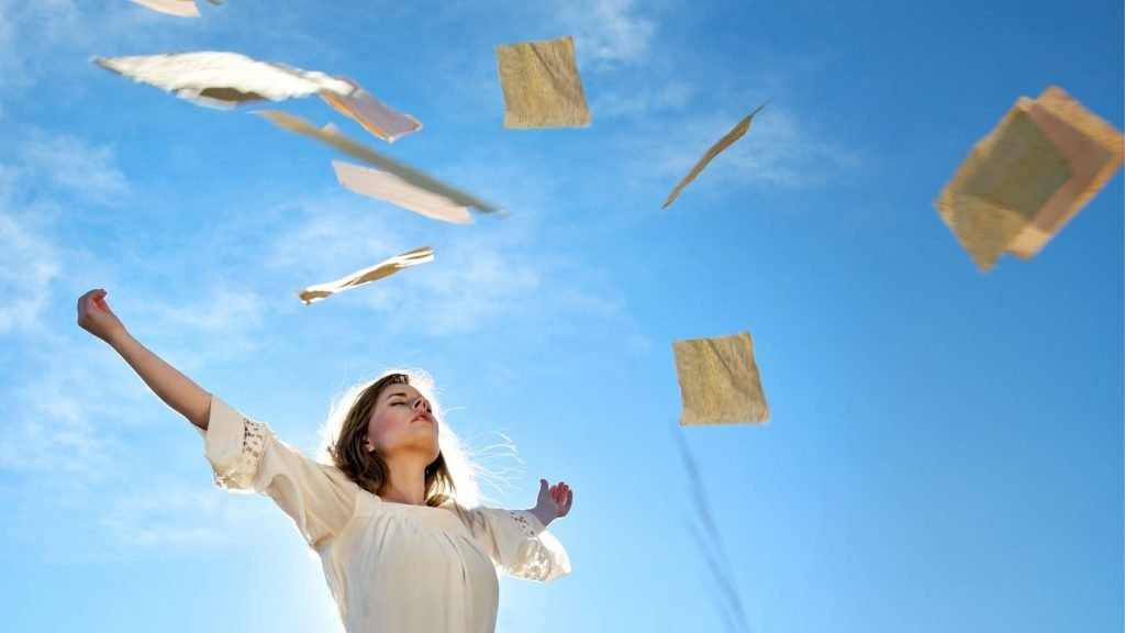 woman letting go of paperwork as it soars into the blue sky, quit taking it personally is one of 3 keys to a lasting marriage