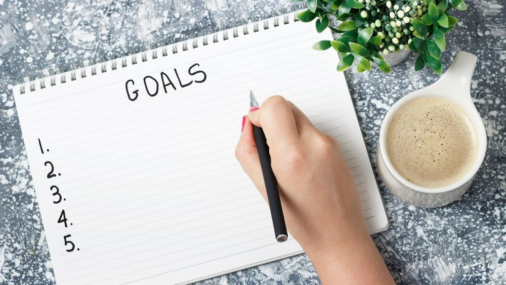 woman's hand writing down goals on pad of paper.  How to begin journaling for personal growth