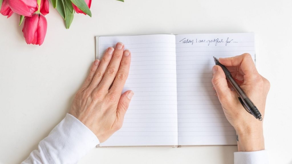 Woman writing about gratitude, how to begin journaling for personal growth
