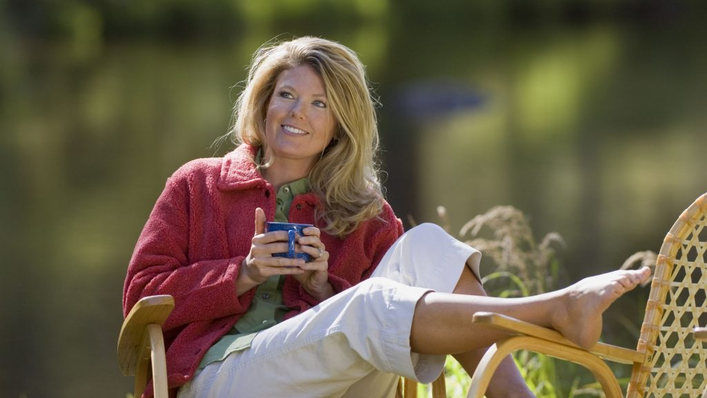 woman relaxing outside barefoot with cup of tea, stress less and sleep well