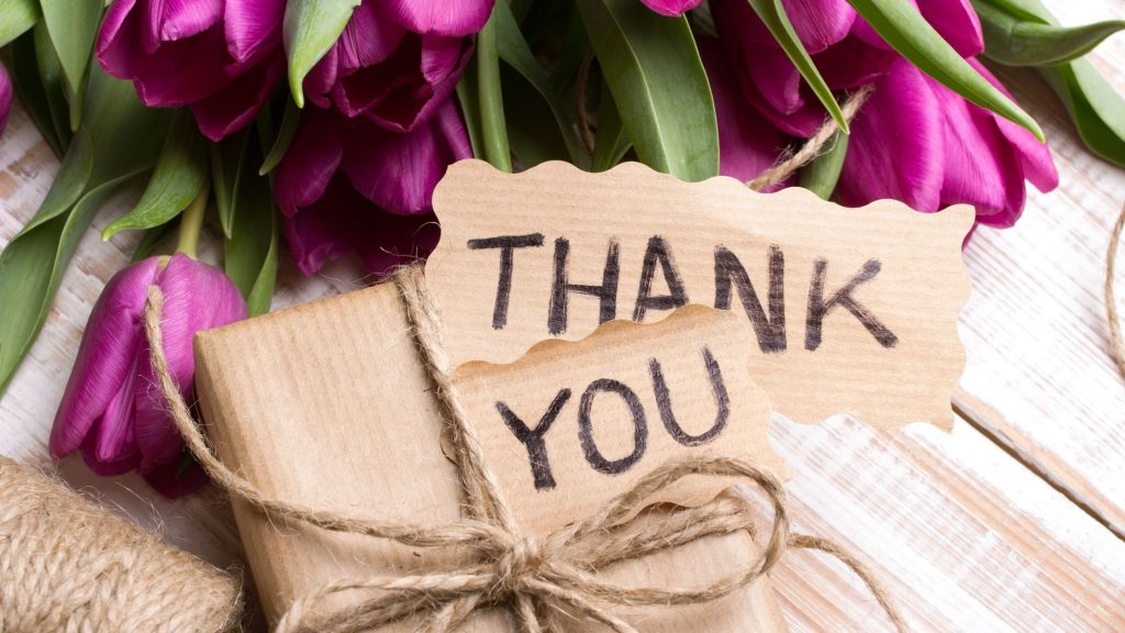 thank you written on kraft paper and tied to a package with twine, next to a bouquet of purple tulips