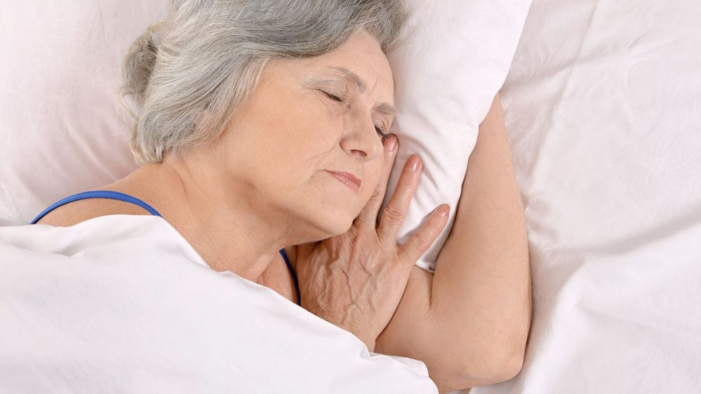woman sound asleep in bed, stress less and sleep well