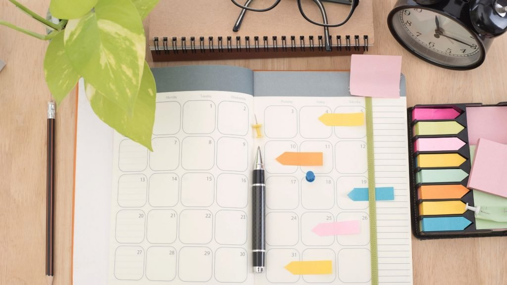 schedule book with pen and color coded stickers, one of four waysto maintain energy throughout a busy day
