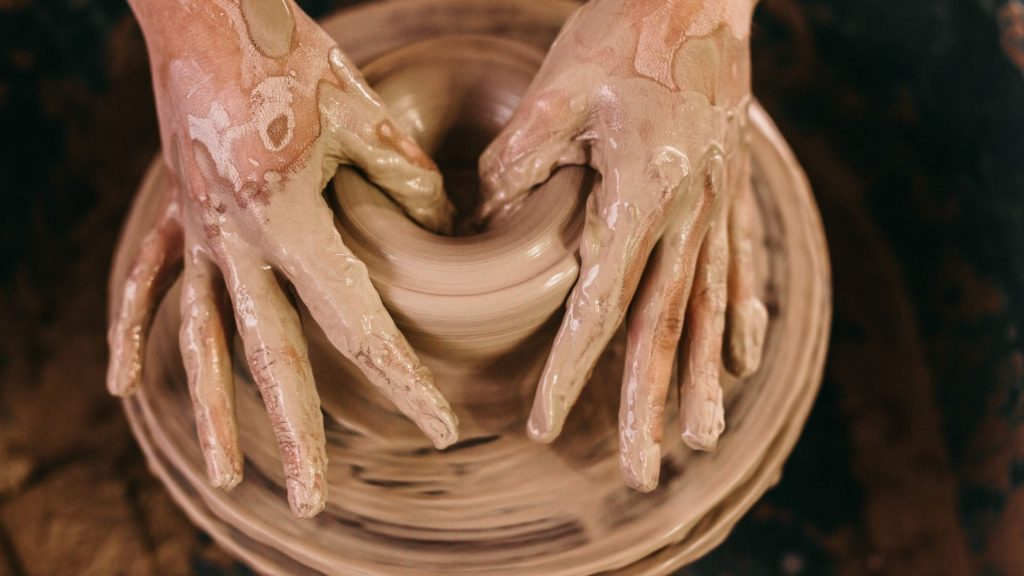 hands creating clay pot on potter's wheel