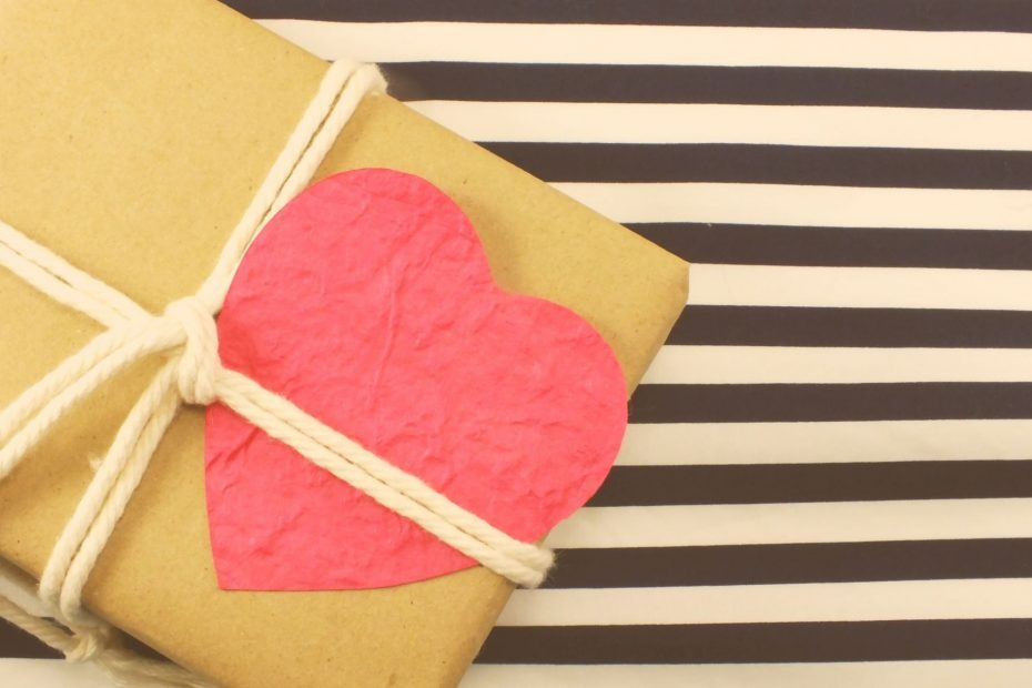 brown paper wrapped package with heart on black and white striped background