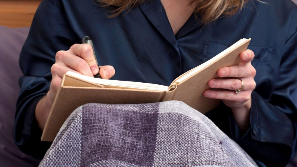 Journaling at Bedtime Can Help You Sleep as this woman in black in bed writing in journal
