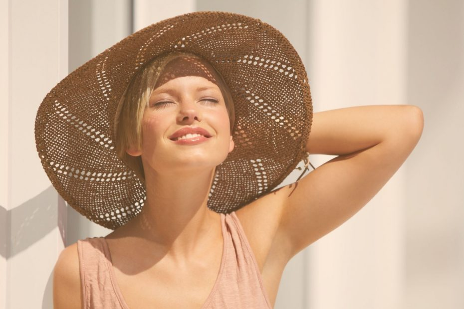 woman in large floppy hat smiling into sunshine