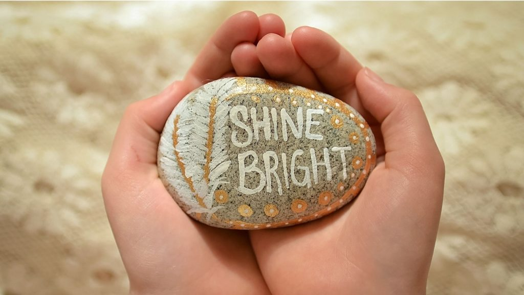 hands cupping rock on which is painted the words:  Shine Bright, daily affirmation.